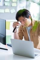 Aziatische zakenman aan het werk met computer op kantoor foto