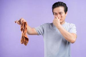 Aziatische man met sokken op paarse achtergrond foto