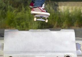 met het skateboard over een obstakel springen foto