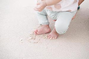kleine voet van babymeisje op zandstrand. voor het eerst op zand lopen. foto