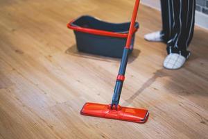 vrouw die de vloer van de woonkamer schoonmaakt door menigte. foto