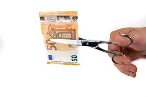 man die bankbiljetten van 50 euro snijdt met een schaar foto