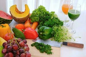 geassorteerde verse rijpe groenten en fruit op tafel bij witte gordijnachtergrond, foto