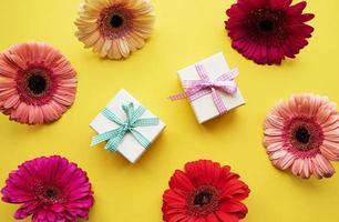 gerbera bloemen en geschenkdozen op een gele foto