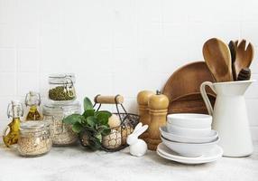 keukengerei, gereedschap en servies op de witte tegelwand als achtergrond foto