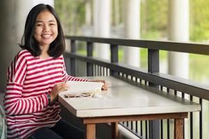 Aziatische student meisje zit en lacht lezen van een boek in de school foto