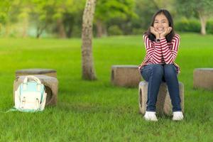 Aziatisch studentenmeisje dat op een zonnige zomerdag in het schoolpark zit te glimlachen foto