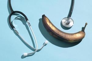 minimale lay-out met een rotte banaan en een traditionele stethoscoop met harde schaduwen foto