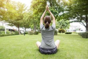 close-up van een vrouw die yoga doet in de groene tuin foto