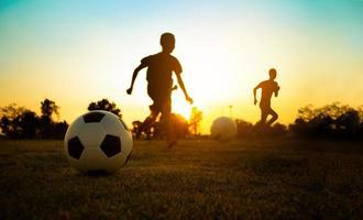 silhouet actie sport buitenshuis van een groep kinderen die plezier hebben met voetballen om te oefenen in het landelijke gebied van de gemeenschap onder de schemering zonsondergang hemel. foto