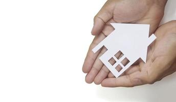 handen met papieren huis, gezinshuis dat verzekeringsconcept beschermt foto