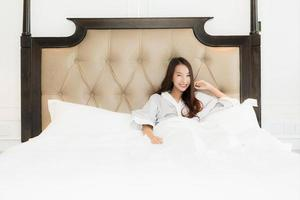 portret mooie jonge aziatische vrouw wakker met blij en glimlach op bed in slaapkamer interieur foto