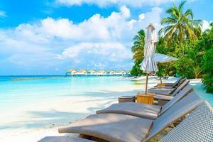 strandstoelen met tropische Malediven resort hotel eiland en zee achtergrond foto