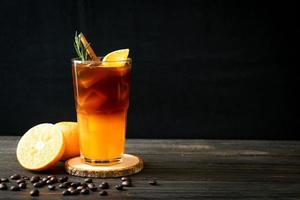 een glas iced americano zwarte koffie en een laagje sinaasappel- en citroensap versierd met rozemarijn en kaneel op een houten ondergrond foto