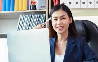 vrouw in een geel pak zit op kantoor en denkt aan marketing foto