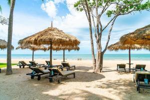 strandstoelen en parasols met oceaan zee strand achtergrond foto