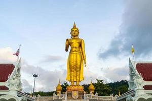 een gouden boeddhabeeld met de lucht op de bergtop in het openbare park van de gemeente Hat Yai, provincie Songkhla, Thailand foto