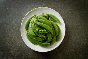 verse zoete groene erwten op witte plaat foto