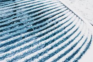 verwarmde de achterruit van de auto in de winter bij vorst - de sneeuw smelt op de ruit van de elektrische verwarming foto