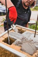 handen van een professionele metselaar tijdens het werken op een bouwplaats - gemetselde muur van een betonblok foto