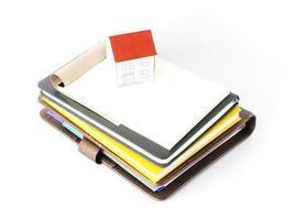 papieren huis op stapel boeken met hierboven op een witte achtergrond foto