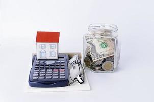 papieren huis met rekenmachine en glazen en flessen geld besparen foto