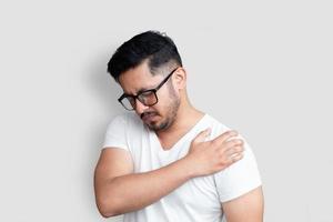knappe jonge man met zwarte bril met pijn in de schouder op witte achtergrond foto