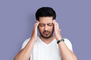 close-up foto van jonge leeftijd man perfecte verschijning armen handen op het voorhoofd. vreselijke pijn in de ogen, gesloten casual wit t-shirt geïsoleerd op de achtergrond