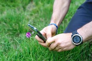 fotografie naar een bloem in de wei met smartphone foto