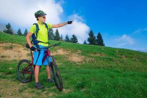 een jonge man die buiten op een mountainbike rijdt, bedekt het pad foto