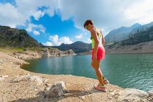 een vrouw rust tussen fitnesstraining in de bergen foto