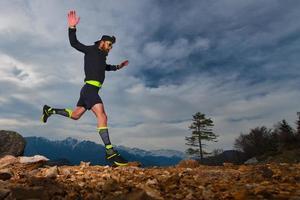 atletische voorbereiding van een man voor trailrunningwedstrijden in de bergen foto