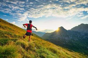 runner skyrunner op een bergweide bij zonsopgang foto