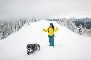 een hond en zijn matresse alleen in de bergen met veel sneeuw foto