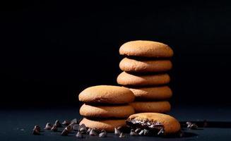 koekjes - stapel heerlijke roomkoekjes gevuld met chocoladeroom op zwarte achtergrond foto