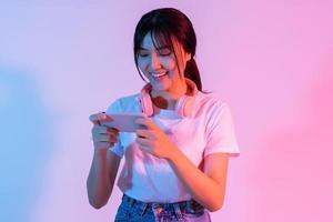 jong Aziatisch meisje speelspel op telefoon met opwinding foto