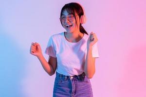 jong Aziatisch meisje draagt een koptelefoon en luistert opgewonden naar muziek music foto
