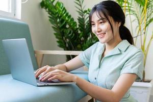 jonge Aziatische vrouw die online vanuit huis werkt foto