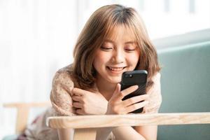 het jonge meisje lag languit op de bank met haar telefoon en glimlachte vrolijk foto
