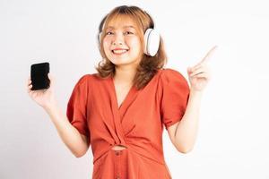jong Aziatisch meisje dat haar telefoon gebruikt en een koptelefoon draagt om van muziek te genieten foto