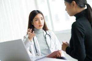 Aziatische vrouwelijke arts onderzoekt patiënten in de kliniek foto