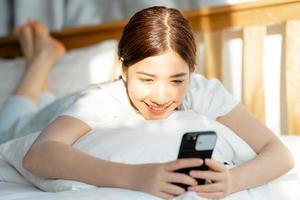 mooie aziatische vrouw die haar telefoon gebruikt als ze net wakker wordt foto