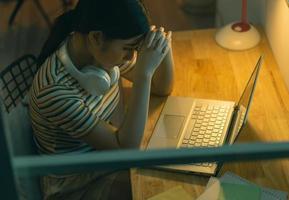 vermoeide aziatische vrouw die 's nachts probeert te werken foto