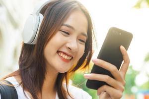 jong Aziatisch meisje dat tekst op haar telefoon leest en een koptelefoon draagt om op straat naar muziek te luisteren foto