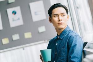 de aziatische man drinkt koffie tijdens zijn pauze en kijkt uit het raam, denkend aan zijn werk foto