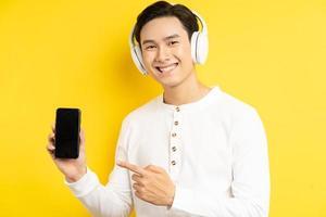 Aziatische zakenman droeg een draadloze koptelefoon om naar muziek te luisteren en zijn vinger wees naar de mobiele telefoon die hij vasthield foto