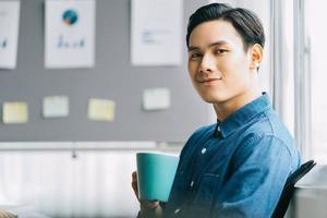 Aziatische man zit en drinkt koffie tijdens de pauze foto