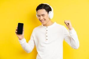 Aziatische zakenman luistert naar muziek met een draadloze koptelefoon, met een ming-smartphone in zijn hand foto