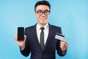 Aziatische zakenman in pak met smartphone en bankkaart bank foto