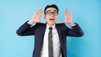 Aziatische zakenman die een kostuum draagt dat op blauwe achtergrond schreeuwt foto